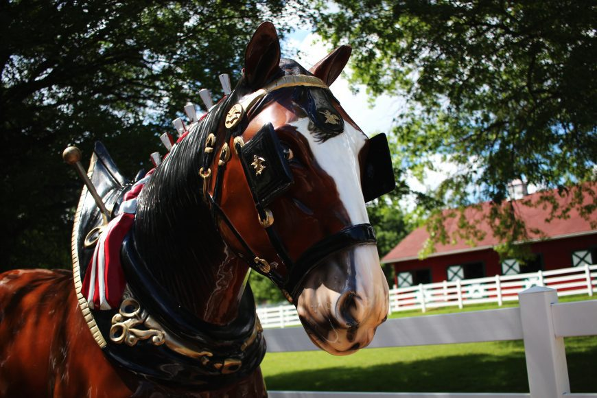 a statue of a Clydesdale in front of a historic building at Grant's Farm in St. Louis, Missouri