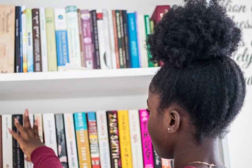 a girl choosing a book off of a shelf