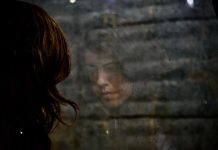 a woman from behind, her image reflected in the window glass that she stands in front of
