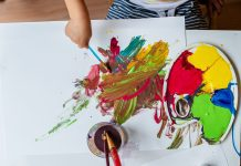 a view from above of a toddler painting on a large white paper with a messy palate of paint and a cup of brushes