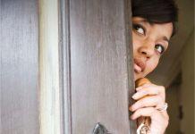 a woman peeking out around a wooden door