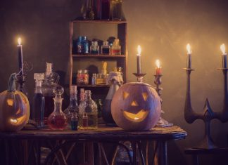 a table with bottles of potions, flanked by lit up jack-lanterns as candles flicker in the background