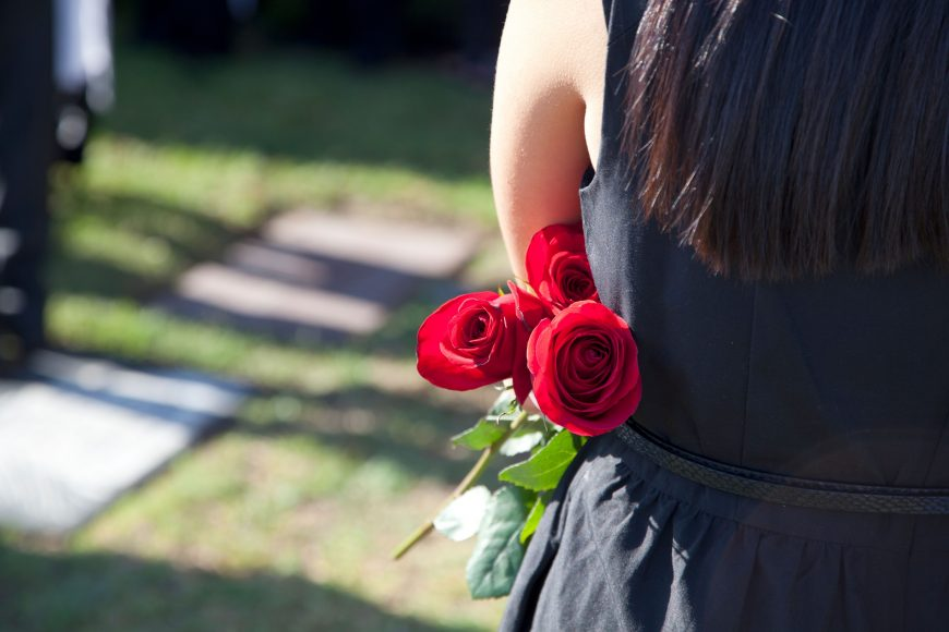 a woman from behind holding roses at a cemetery as she deals with death and grieving